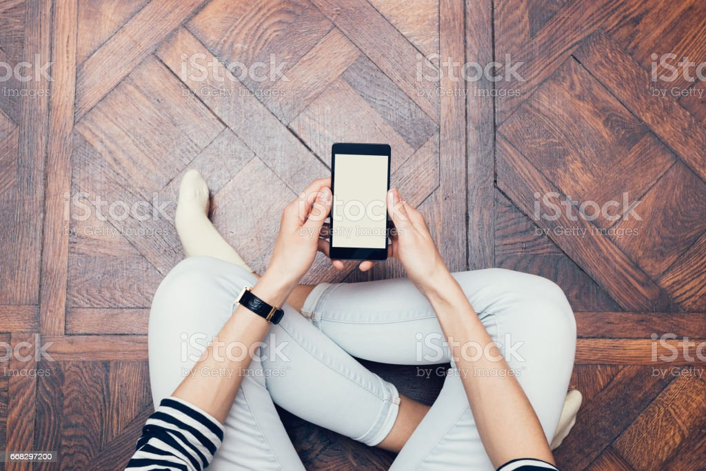 Girl in jeans sitting on the floor at home and using a mobile phone stock photo