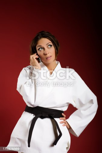 beautiful girl in kimono and black belt speaking on mobile phone