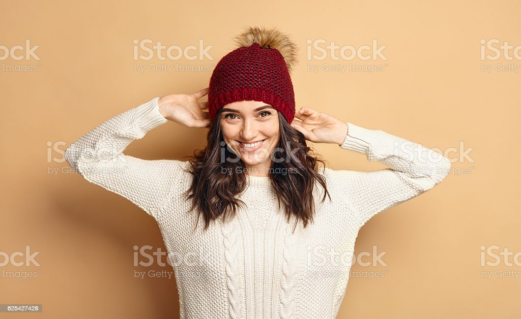 Girl in Knitted Sweater and Beanie Hat over beige background - Photo