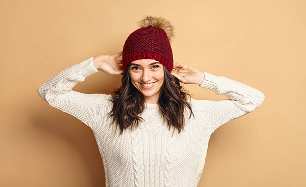 Girl in Knitted Sweater and Beanie Hat over beige background stock photo