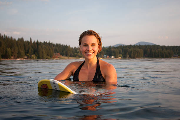 Girl in lake sitting on a surfboard at sunset stock photo