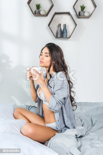 beautiful young woman with closed eyes sitting on bed and drinking coffee