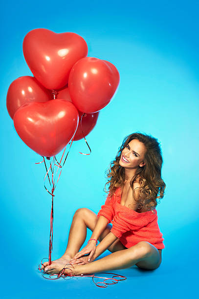 Girl in lingerie holding red heart shaped balloons stock photo