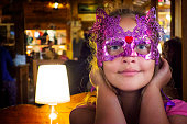 Beautiful Girl in a Carnival mask in the restaurant.