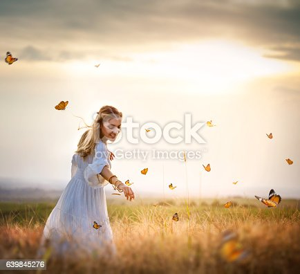 istock Girl in meadow with flitting butterflies 639845276