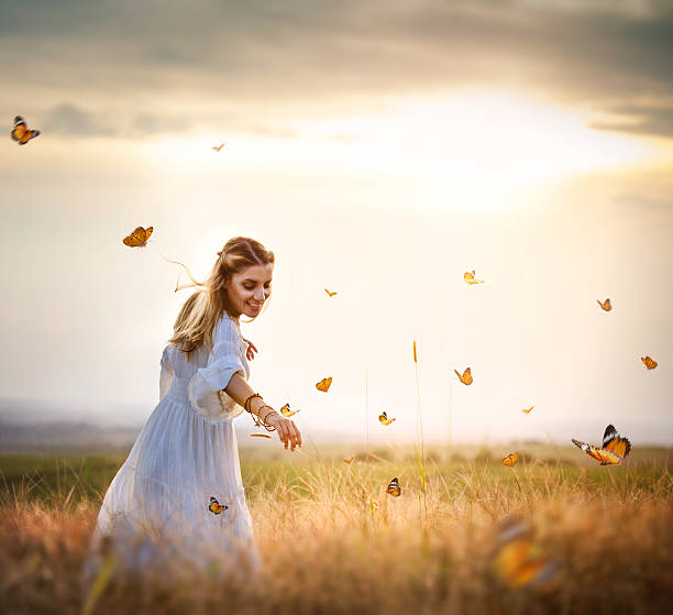 girl in meadow with flitting butterflies - mariposa fotografías e imágenes de stock