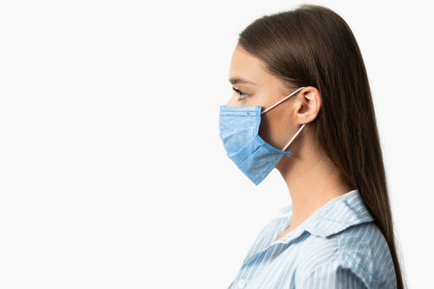 Mädchen in medizinische Maske posiert auf weißen Studio Hintergrund, Seitenansicht – Foto