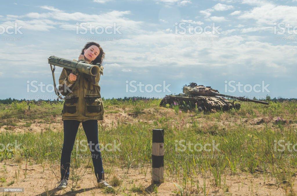 chica en uniforme militar y pantalones vaqueros con una bazuca en sus manos - foto de stock