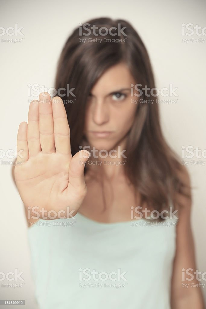 A girl in mint top with a stop gesture looking at the camera stock photo