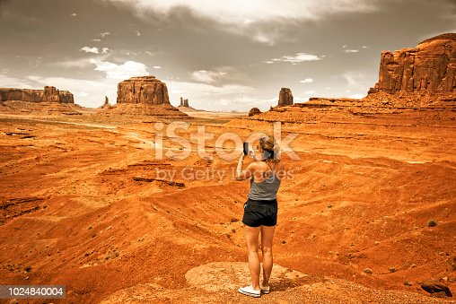Young woman is taking a photo of Monument Valley