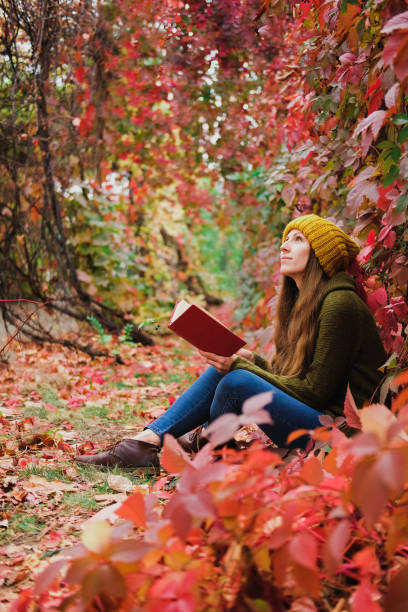 Girl in mustard yellow knit hat and marsh green wool sweater sitting among colorful ivy in autumn and reading a paper book stock photo