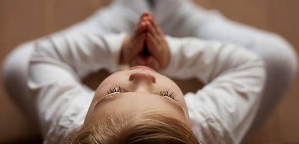 Girl in Namaste Yoga prayer pose stock photo