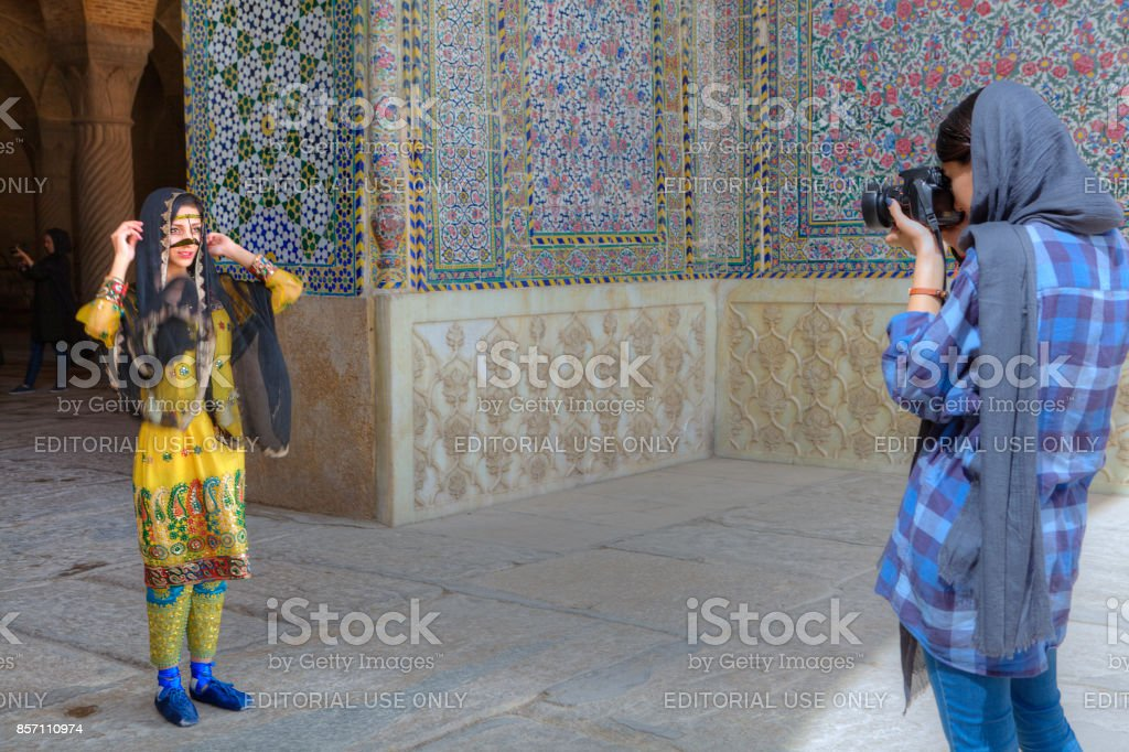 Girl in national costume posing for woman photographer Shiraz, Iran. stock photo
