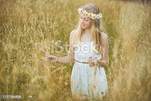 Smiling young girl in tall grass picking flowers.