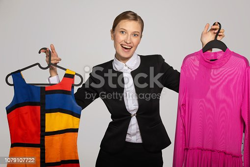 672064598istockphoto Girl in office suit holding colored dresses 1079107722