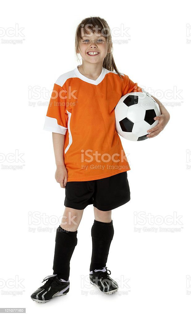 Girl in orange and black uniform with soccer ball stock photo