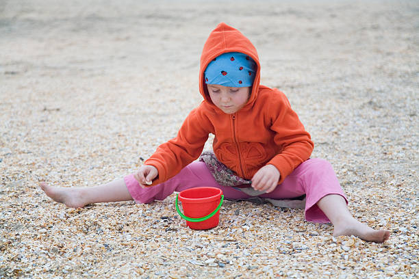 girl in orange at the beach, collecting shells - little girl picking up sea shells at the beach stock pictures, royalty-free photos & images