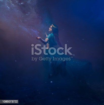 istock A girl in oriental attire, Queen of the storm. Princess Jasmine. The background is a twist and a strong wind. Studio shooting with mixed light. Artistic Photography 1085073722