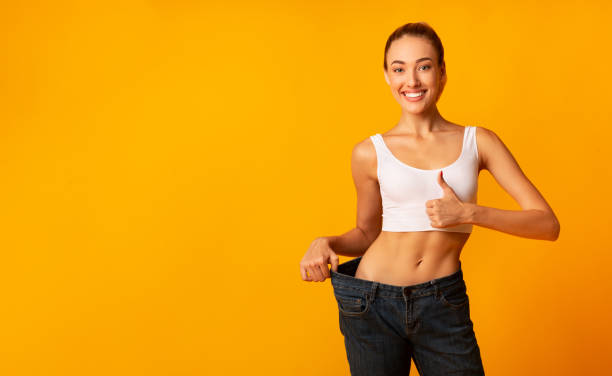 Girl In Oversize Jeans Gesturing Thumbs Up Smiling, Yellow Background Weight Loss. Girl In Oversize Jeans Gesturing Thumbs Up Smiling At Camera Standing On Yellow Studio Background. Copy Space dieting stock pictures, royalty-free photos & images