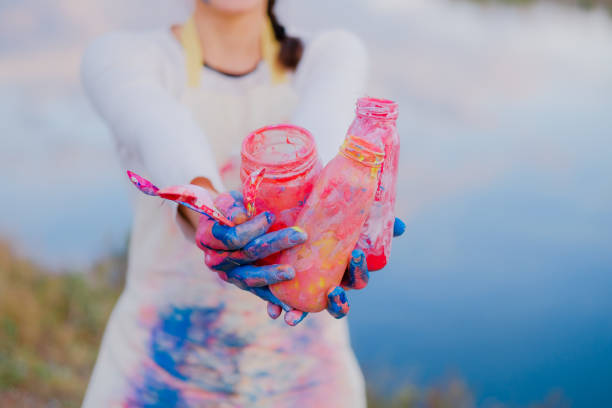 Girl in painted apron holding brushes and jar. Female artist outdoors stock photo