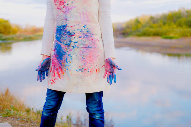 Girl in painted apron with dirty hands. Female artist outdoors stock photo