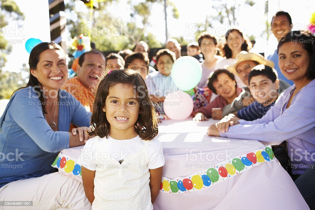 Girl (4-6) in park celebrating party with extended family royalty-free stock photo