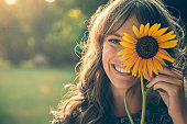 Girl in park smiling and covering face with sunflower
