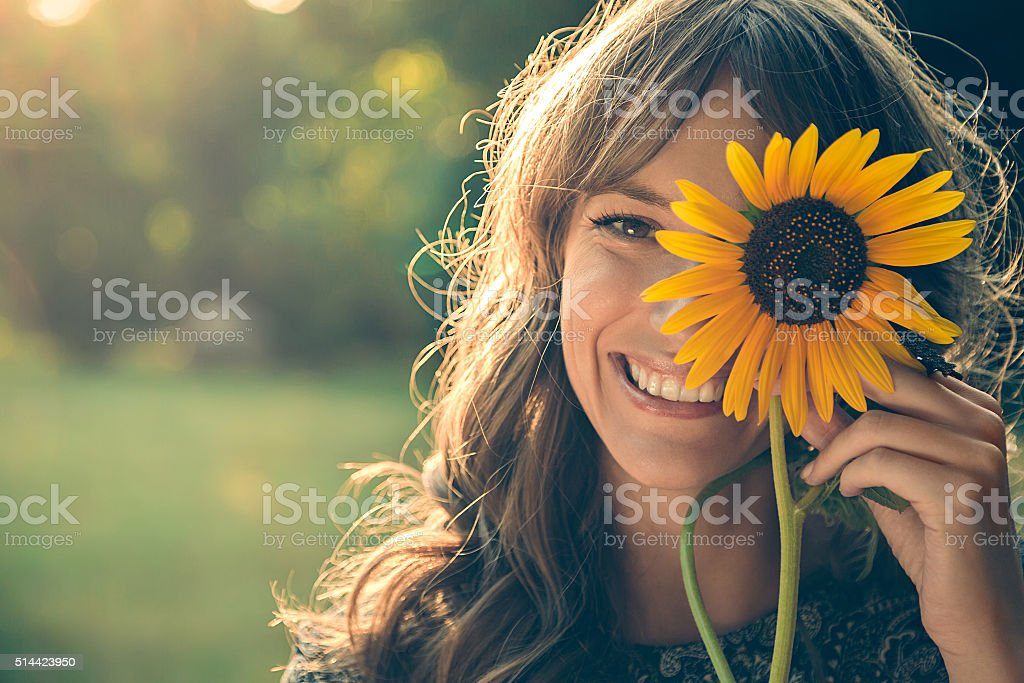 Girl in park covering face with sunflower stock photo