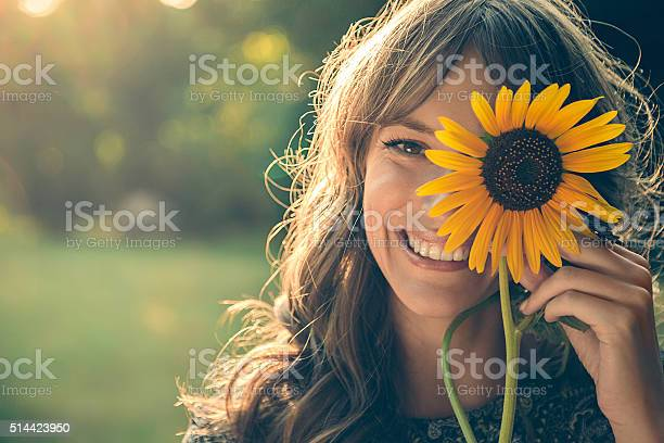 Photo of Girl in park covering face with sunflower