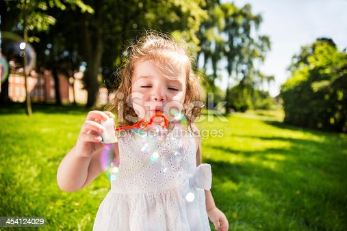 istock Girl in park having fun blowing bubbles 454124029