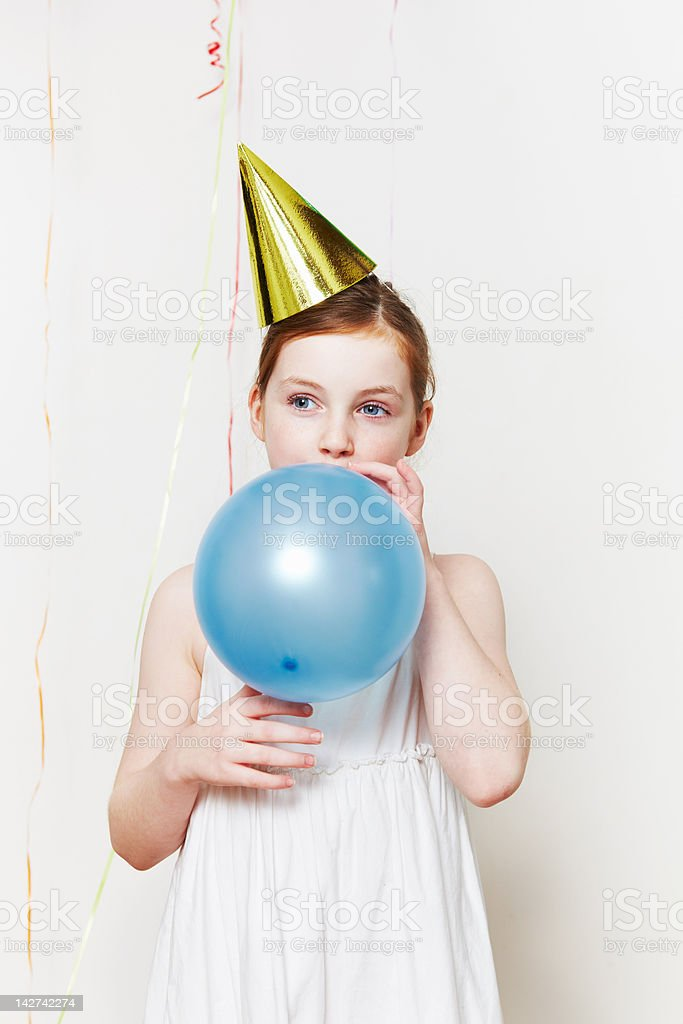 Girl in party hat, blowing up balloon stock photo