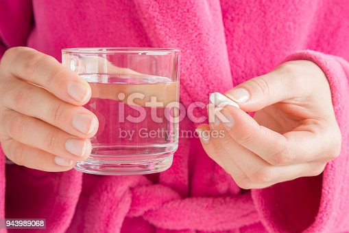 istock Girl in pink bathrobe. Hands holding a glass of water and white pill. Receiving vitamins or medicaments. Women's issues. Medical, pharmacy and healthcare concept. 943989068