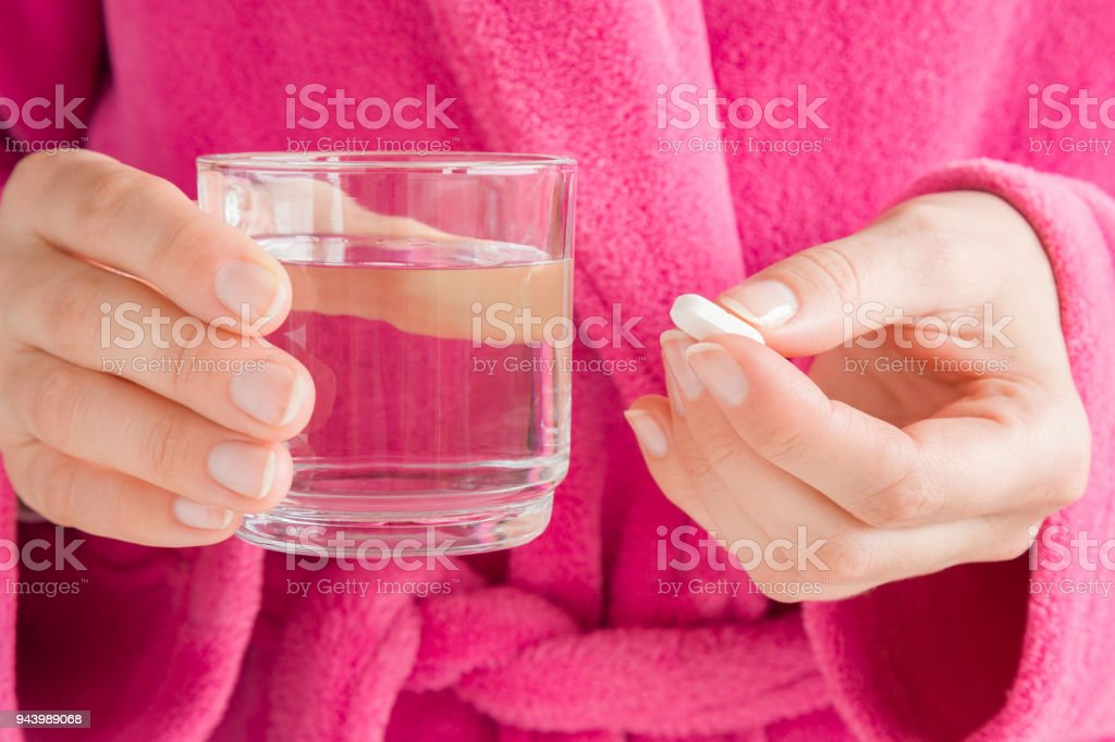 Girl in pink bathrobe. Hands holding a glass of water and white pill. Receiving vitamins or medicaments. Women's issues. Medical, pharmacy and healthcare concept. stock photo