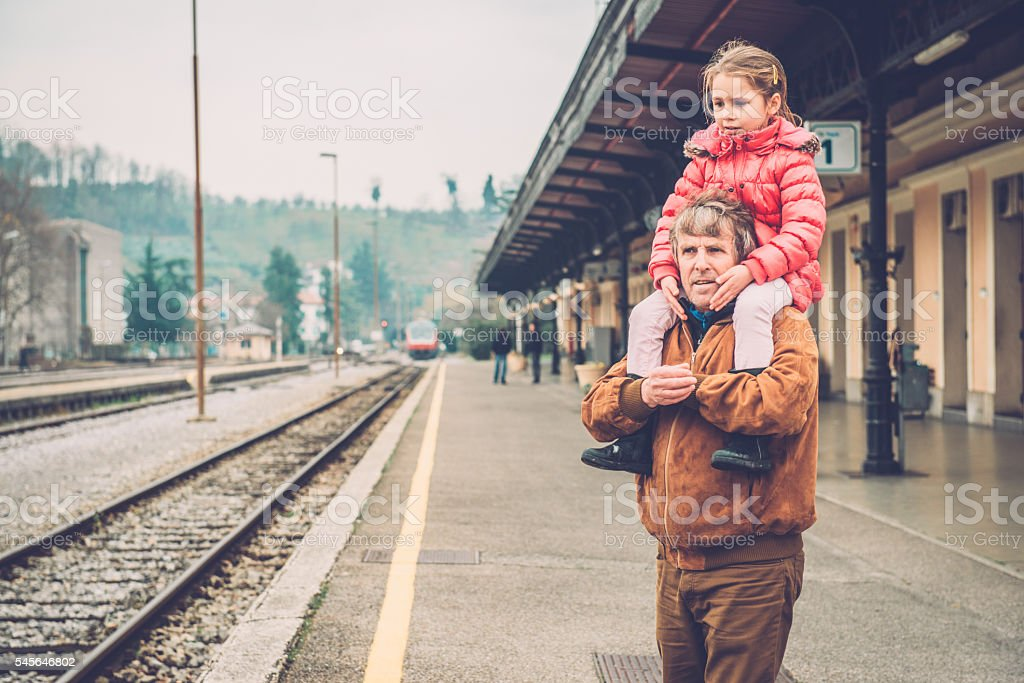 Girl in Pink Riding on Grandfather's Shoulder, Railway Station, Europe stock photo