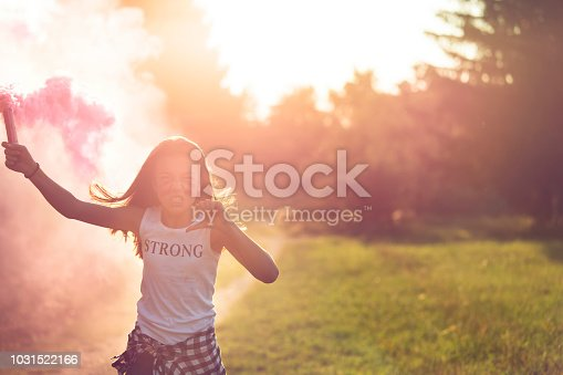 istock Girl in pink smoke 1031522166