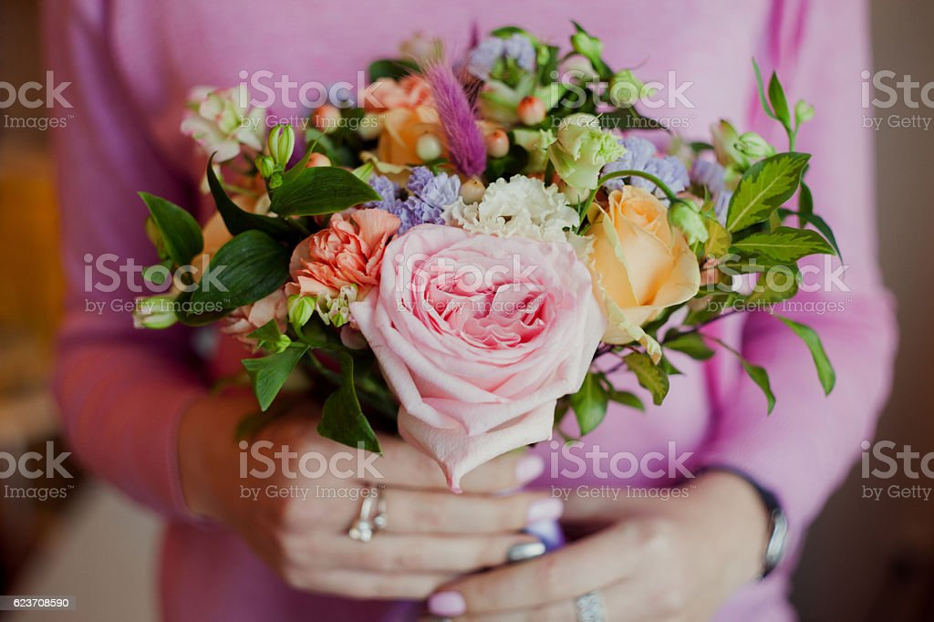 Girl in pink sweater holding a beautiful lush bouquet with stock photo