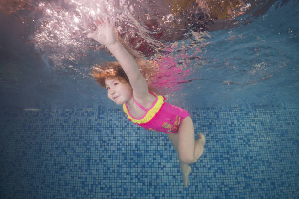 Girl in pink swimsuit playing underwater in the pool floats and spins among the air bubbles. Healthy family lifestyle and children water sports activity. Child development, disease prevention stock photo