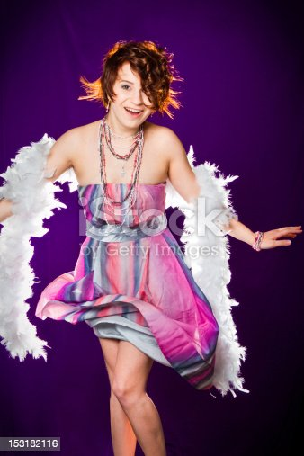 beautiful girl with pink dress and white boa posing on purple background