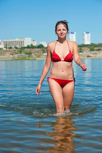 1155046257 istock photo Girl in red bikini exit from river 485688880