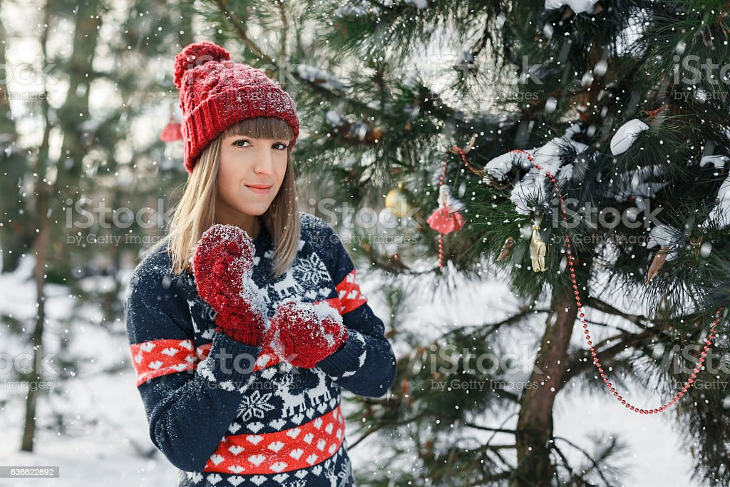 Girl in red cap and mittens standing near Christmas tree stock photo