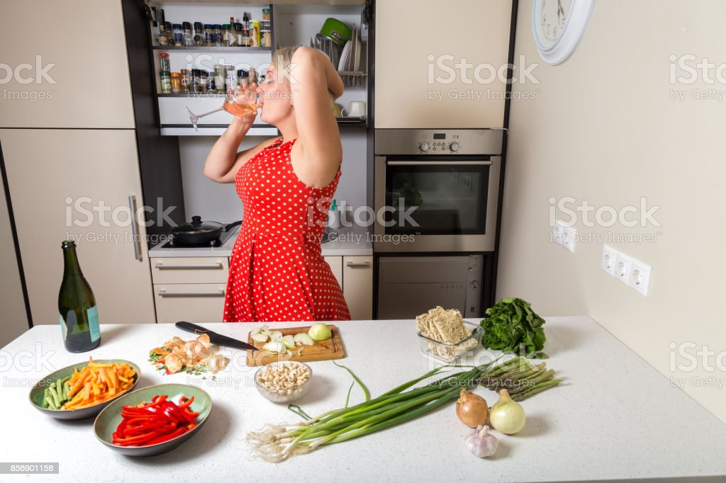 Girl in red dress drinking wine from glass in kitchen stock photo