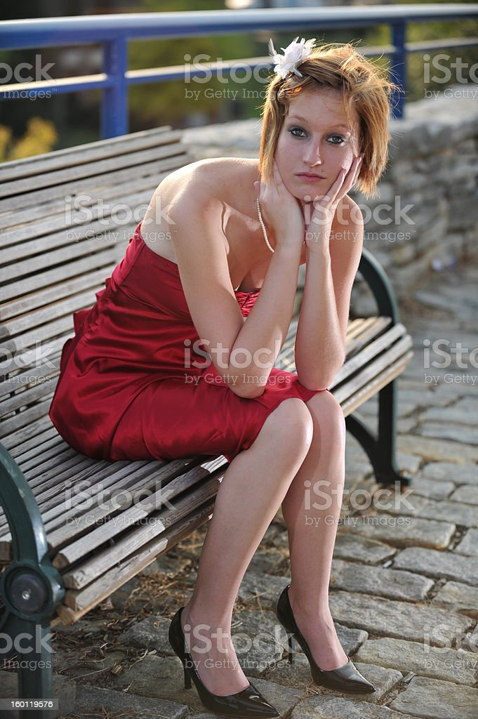 Girl in Red Dress Sitting on Bench royalty-free stock photo