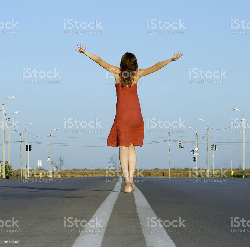 girl in red dress walk barefoot on empty road stock photo