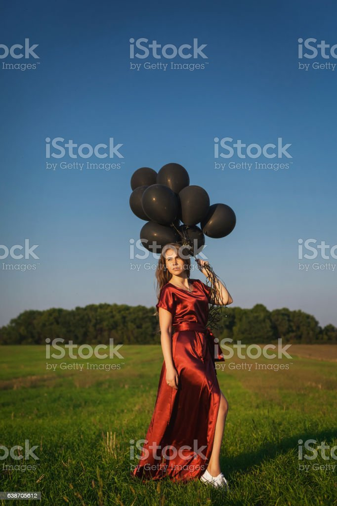 girl in red dress with black balloons standing in a stock photo