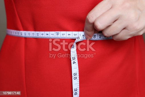 1163494373 istock photo Girl in red dress with measuring tape around the waist 1079617140