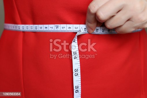 1163494373 istock photo Girl in red dress with measuring tape around the waist 1090563354