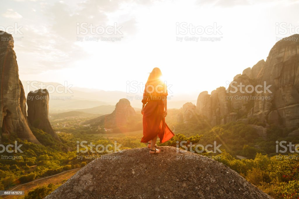 Girl in red flying dress looking at majestic sunset in Meteora valley, Greece stock photo