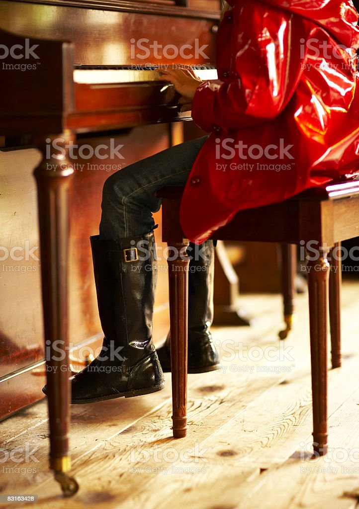 Girl in red raincoat playing piano royalty free stockfoto