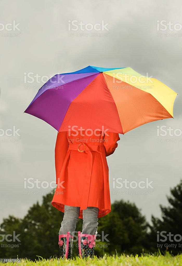 Girl in red raincoat standing under a multicolored umbrella royalty-free stock photo