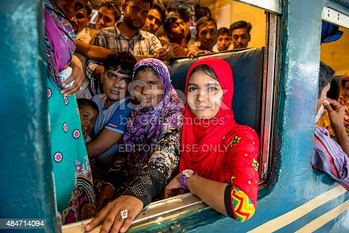 Dhaka, Bangladesh - July 16,2015: A girl in red is sitting at the window of a crowded compartment, which is about leaving Dhaka, the capital of Bangladesh.